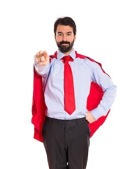 Uomo d'affari vestito come supereroe che punta alla parte anteriore
