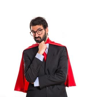 Uomo d'affari vestito come supereroe pensando oltre bianco