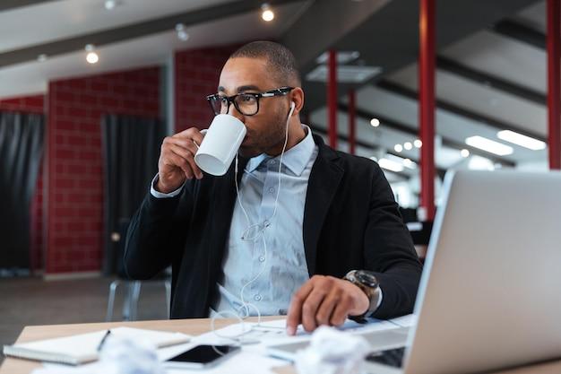 Бизнесмен пьет и слушает музыку в офисе с ноутбуком