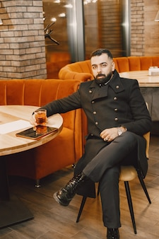 Бизнесмен, пьющий в кафе