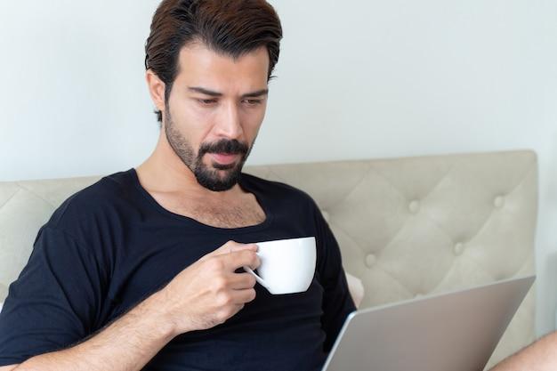 Uomo d'affari che beve caffè durante il lavoro in ufficio a casa
