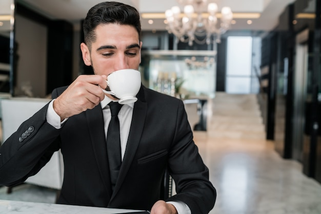 Businessman drinking coffee at hotel lobby.