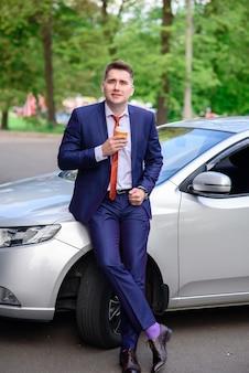Бизнесмен пьет кофе в машине.
