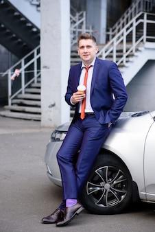 Businessman drinking coffee near the car.