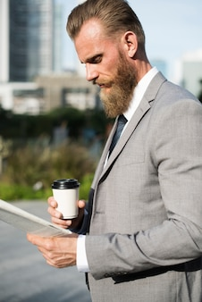 Businessman drinking a coffee and reading a newspaper in the morning commute