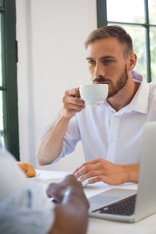 Businessman drinking coffee at table in restaurant