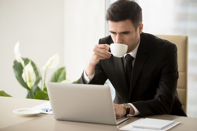 ビジネスマンのオフィスで働くときにコーヒーを飲む