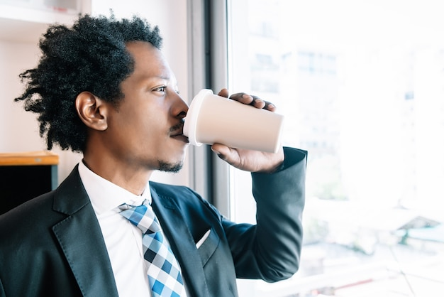Businessman drinking a cup of coffee while taking a break from work at his office. business concept.