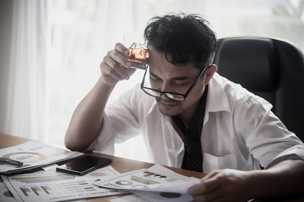 Businessman drinking from stress at workplace