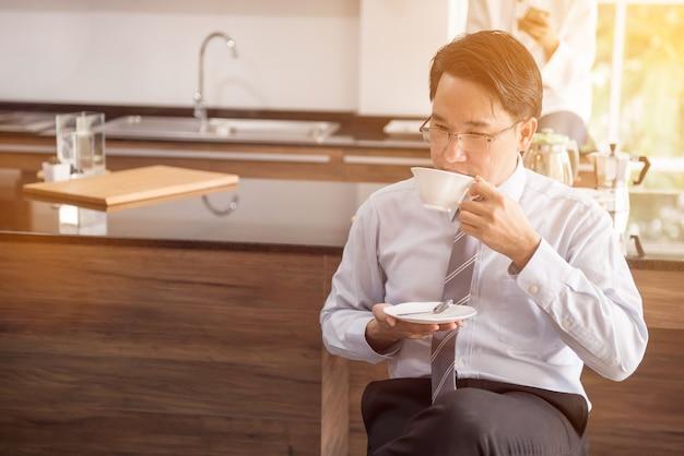 仕事の前に朝にホットコーヒーを飲むビジネスマン。