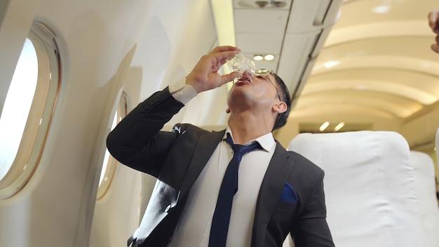 Бизнесмен пьет воду в самолете