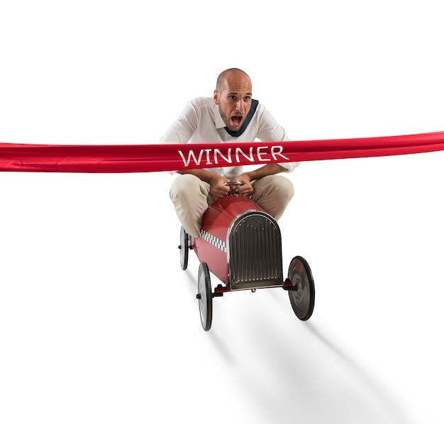 ビジネスマンはレースの到着時に赤いリボンを越えておもちゃの車を運転します