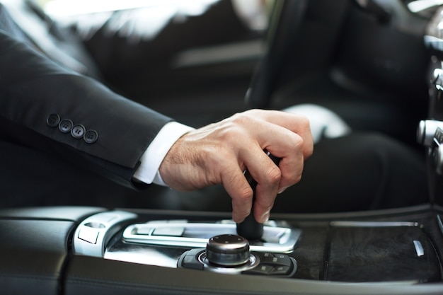 Businessman driving his car on background. close-up human hand holding gear shift knob