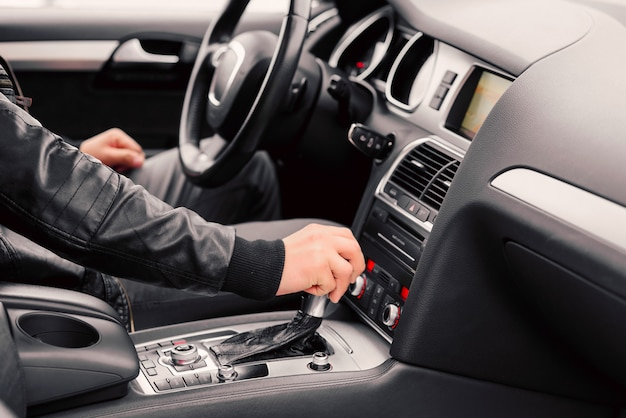 Бизнесмен за рулем роскошного современного автомобиля в городе. закройте мужскую руку на коробке передач.
