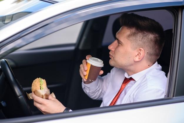Бизнесмен ест гамбургер и пьет кофе в машине.