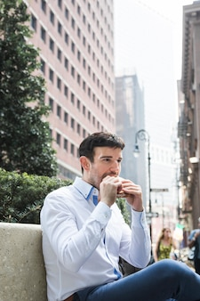 Businessman eating on bench