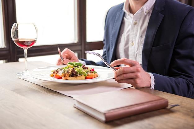 레스토랑에서 비즈니스 점심 식사 시간 동안 먹는 사업가.