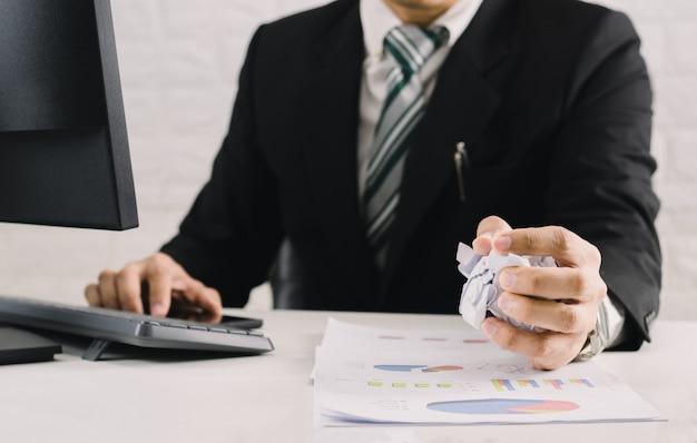 実業家の感情とテーブルの上の紙をくしゃくしゃに失敗した概念の失敗、オフィスで紙を投げて考えて不幸な