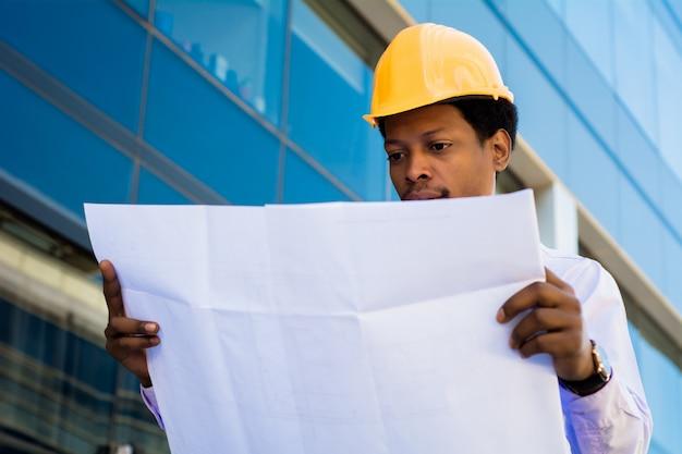 Businessman engineer developer holding blueprint