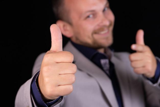ビジネスマン、黒の背景に灰色のスーツを着たエンジニアは、テキストに指を指しています。ビジネスアイデア、コンセプト。