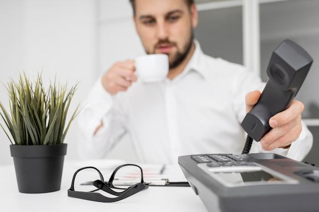 Бизнесмен, наслаждаясь кофе в офисе