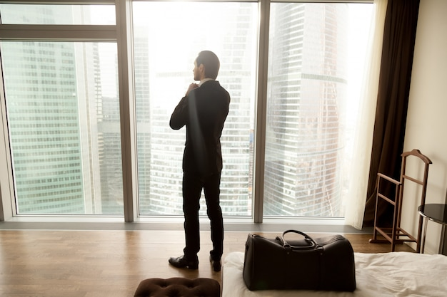 ビジネスマンはホテルの部屋の窓からの眺めを楽しんでいます