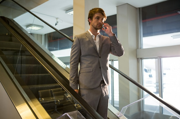 Businessman on escalator talking on mobile phone