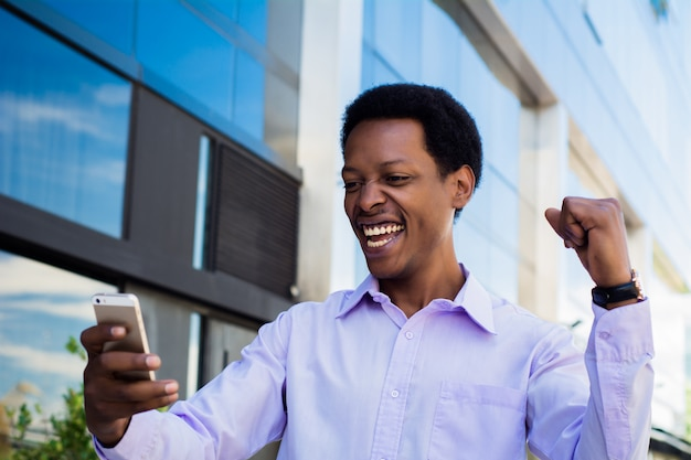 Businessman excited  looking at cell phone.