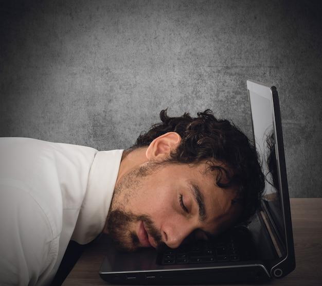 Бизнесмен истощен от переутомления, спит за компьютером