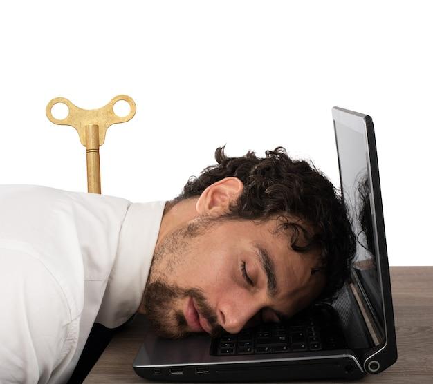 コンピューターで寝ている過労で疲れ果てたビジネスマン