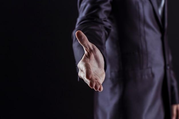 ビジネスマンは握手のために手を前方に伸ばします。