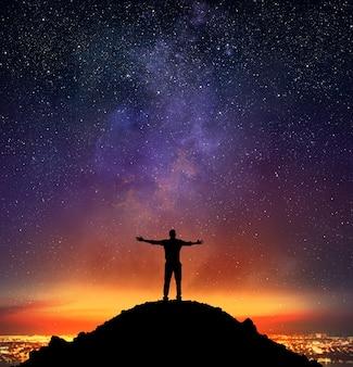 ビジネスマンは星空の山で歓喜します