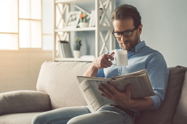Businessman in eyeglasses is reading a newspaper
