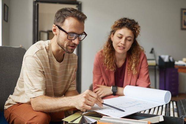 Businessman in eyeglasses sitting at the table pointing at blueprint and discussing it with his colleague at office
