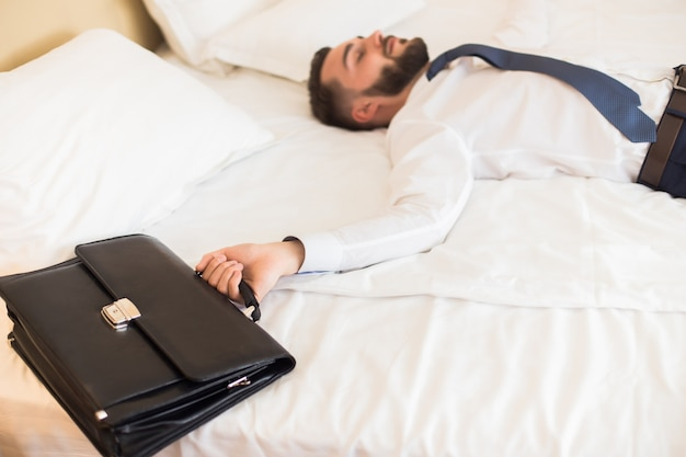 Businessman falling on bed after bad day