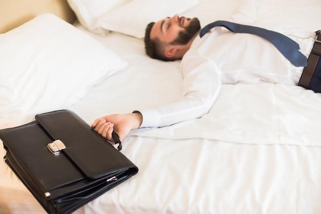 나쁜 하루 후 침대에 떨어지는 사업가