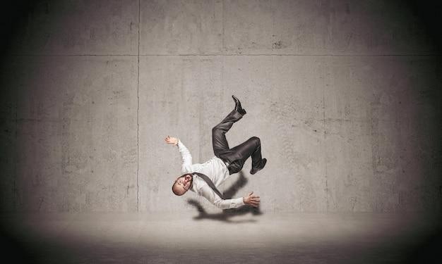 Бизнесмен падает на бетонный фон.