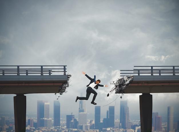 ビジネスマンは壊れた橋をジャンプして倒れます。危機の概念