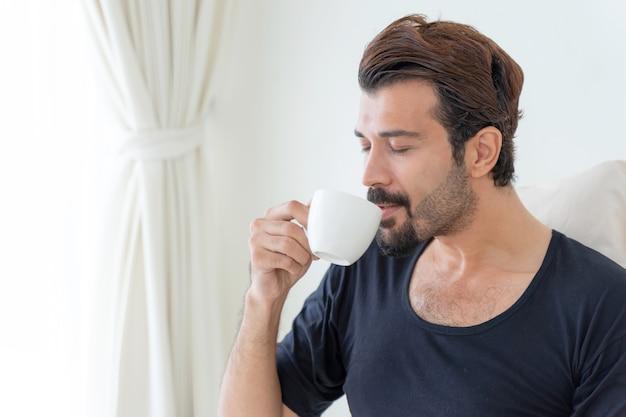Uomo d'affari si sente felice di bere il caffè durante il lavoro a casa