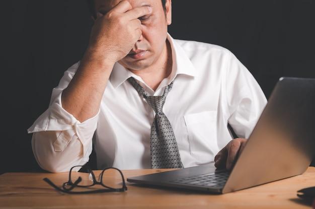 ビジネスマンは、貧しい経済状況のために頭痛を感じ、ハードワークからストレスを感じています
