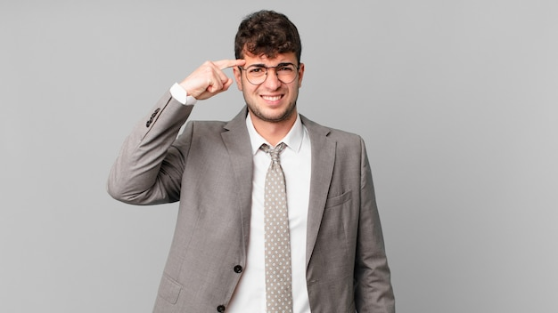 Businessman feeling confused and puzzled, showing you are insane, crazy or out of your mind
