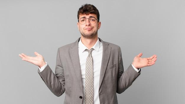 Бизнесмен, чувствуя себя озадаченным и сбитым с толку, сомневаясь, взвешивая или выбирая разные варианты с забавным выражением лица