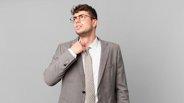 Бизнесмен чувствует стресс, тревогу, усталость и разочарование, дергает за шею рубашки, выглядит разочарованным из-за проблемы