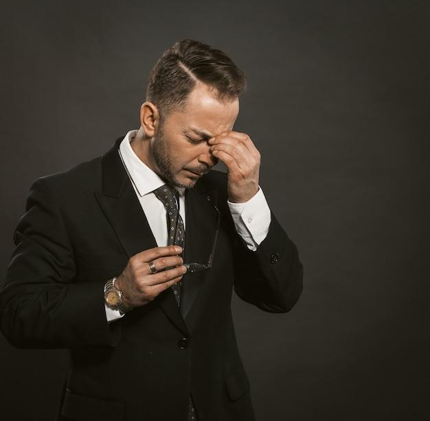 ビジネスマンは頭痛を感じています。灰色の背景の上に立っている間彼の手で鼻の橋と額に触れる白人の男。右側のスペースをコピーします。トーン画像