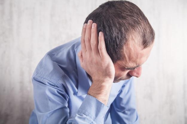 Бизнесмен чувствует боль в ушах. здравоохранение и медицина