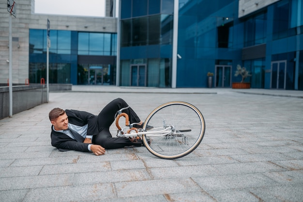 Businessman fell off his bike at the office building in downtown. business person riding on eco transport on city street