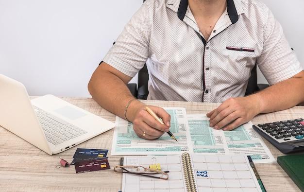 Бизнесмен заполняет налоговую форму 1040 с помощью ноутбука и калькулятора