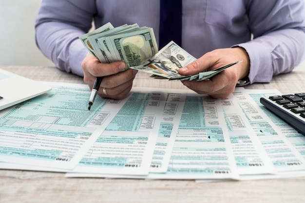 A businessman fills out an individual 1040 tax form and counts dollars. male hands writing on paper with calculator in office. accounting concept