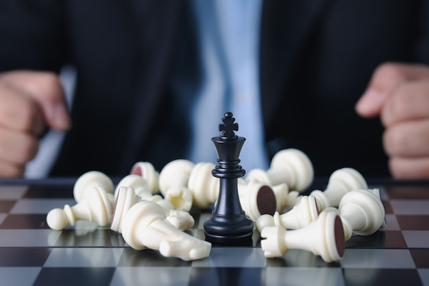 Businessman finger hands control chess king to success position on competition business game with falling enemy chess