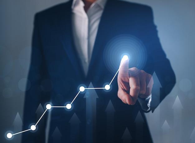 Бизнесмен палец указывая график стрелки. развитие бизнеса к успеху, прибыли и плану роста.